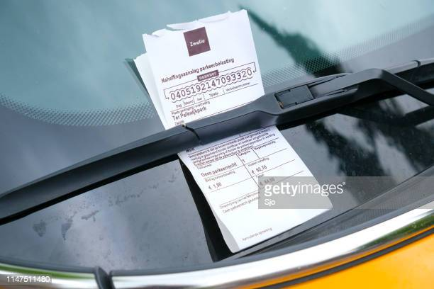 Parking ticket on the windscreen of a car parked on the streets of Zwolle