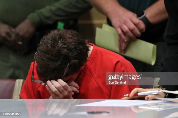 Parkland school shooter Nikolas Cruz takes off his glasses and wipes his eyes during a hearing at the Broward Courthouse in Fort Lauderdale on Friday...