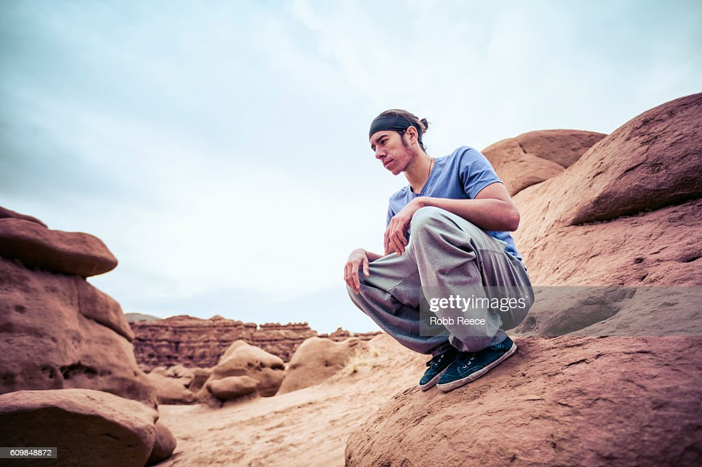 A parkour athlete outdoors on rock formations in the desert : Stock Photo
