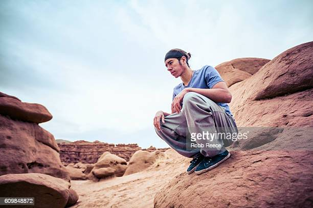 a parkour athlete outdoors on rock formations in the desert - robb reece stockfoto's en -beelden