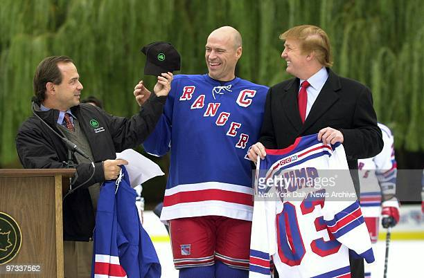 Parks Commissioner Adrian Benepe presents New York Rangers' captain Mark Messier with a cap as Donald Trump holds a Rangers jersey bearing his name...