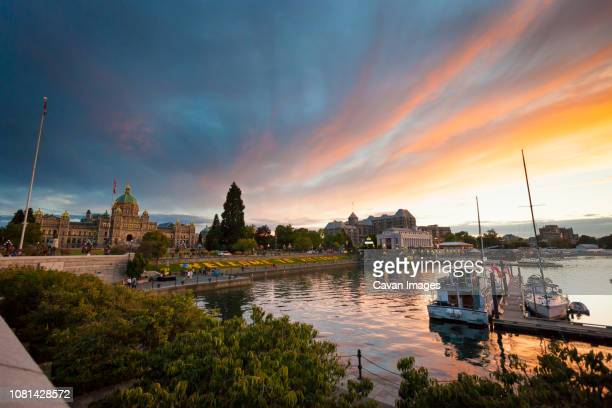 parliament building by harbor in city against dramatic sky during sunset - カナダ ビクトリア市 ストックフォトと画像