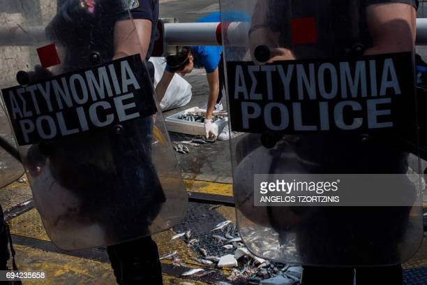 TOPSHOT A parliament employee cleans the main entrance of the Greek parliament guarded by police officers on June 9 after members of the...