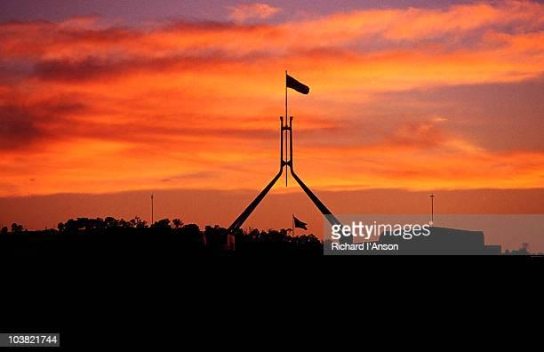 parliament house flag silhouetted at sunset. - オーストラリア国会議事堂 ストックフォトと画像
