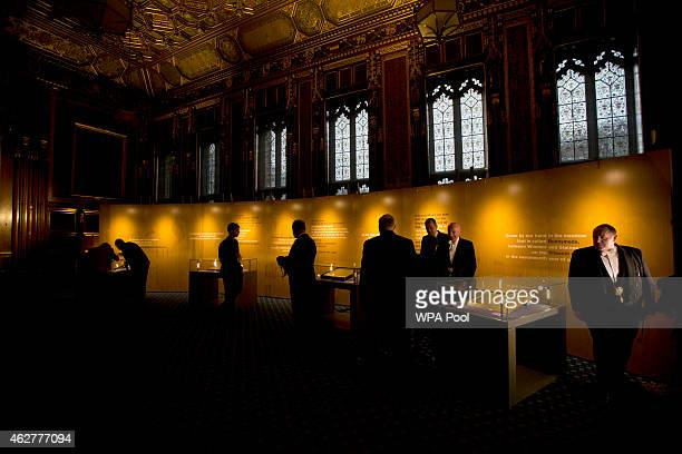 Parliamentary doorkeepers look at the four surviving original parchment engrossments of the 1215 Magna Carta as they are displayed to mark the 800th...