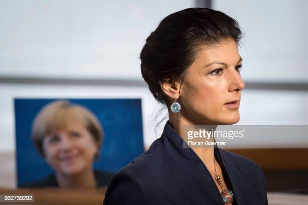 Parliamentary group coleader of Die Linke party Sahra Wagenknecht is pictured in front of a photo of German Chancellor Angela Merkel during an...