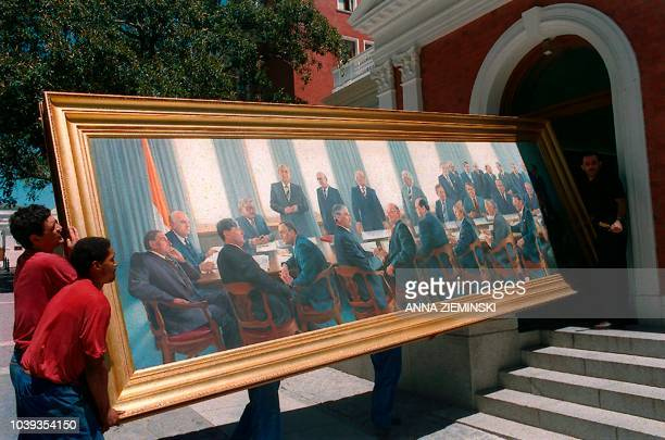 Parliamentary workers remove a painting representing icons of apartheid Pieter Willem Botha and allwhite cabinet from parliament on January 25 in...