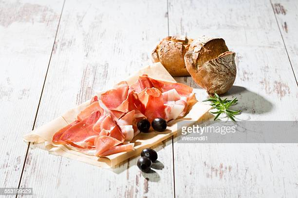 Parma ham on greaseproof paper, rolls and black olives on bright wood