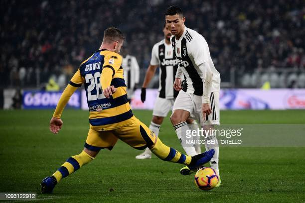 Parma's Italian defender Riccardo Gagliolo tackles Juventus' Portuguese forward Cristiano Ronaldo during the Italian Serie A football match Juventus...