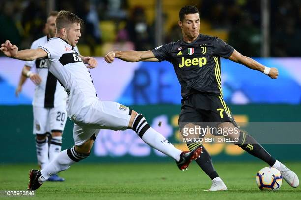 TOPSHOT Parma's Italian defender Riccardo Gagliolo vies with Juventus' Portuguese forward Cristiano Ronaldo during the Italian Serie A football match...