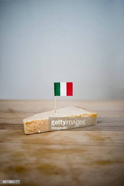 Parmesan cheese with small italian flag on wood