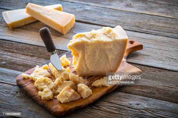 parmesan reggiano cheese on cutting board - parmesan cheese stock pictures, royalty-free photos & images