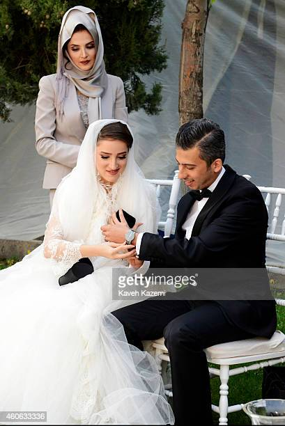 Parmis Taheri and Mostafa Aghaei exchange presents during their wedding ceremony at the social club of Mining Industry Bank on May 1 2014 in Tehran...