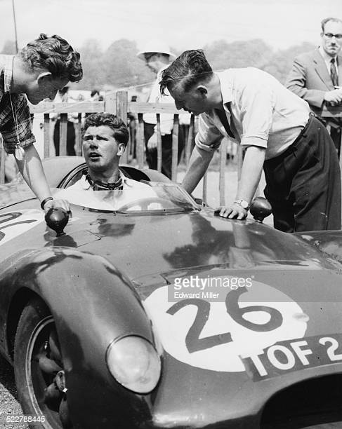 R H Parnell the son of famed racing driver Reg Parnell sitting in a car chatting to mechanics prior to the start of a race in Crystal Palace London...