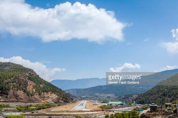 paro international airport, bhutan on a sunny spring afternoon - paro stock photos and pictures