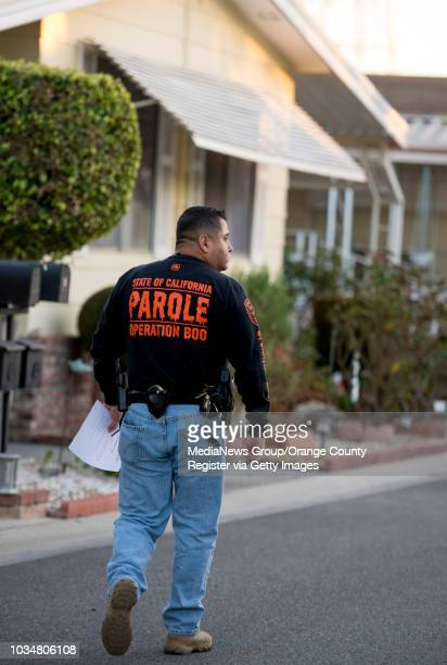 Parole agent George Meza walks to a home to give a set of instructions to a sex offender on parole as part of Operation Boo INFORMATION...