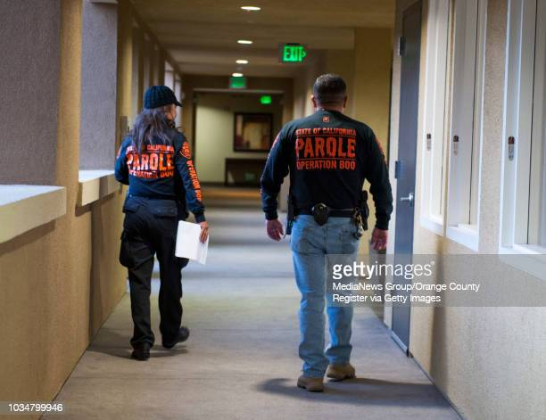 Parole agents Jessica Latumeten left and George Meza walk the corridors of an Anaheim apartment complex after completing a compliance check on a...