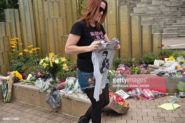 Paroo Streich holds a shirt of boxing legend Muhammad Ali as she pays her respects at the Muhammad Ali Center on June 4 2016 in Louisville Kentucky /...