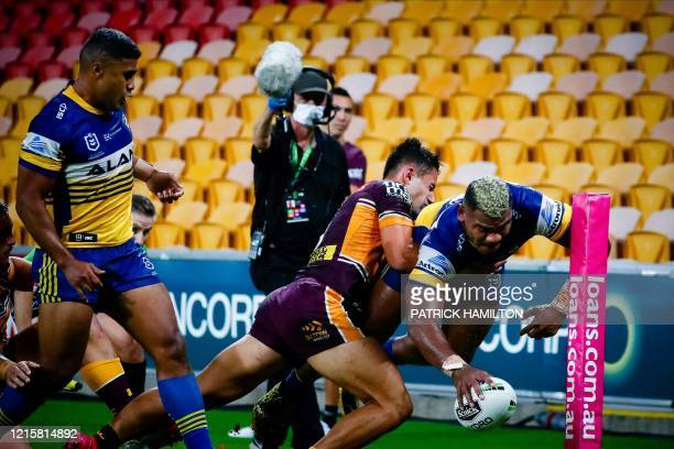 Parramatta Eels' player Maika Sivo scores a try as he is tackled by Brisbane Broncos' player Jesse Arthars during the Australian Rugby League match...