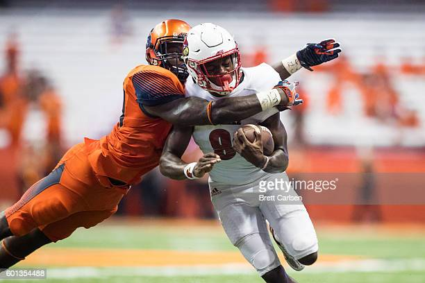 Parris Bennett of the Syracuse Orange tackles Lamar Jackson of the Louisville Cardinals during the second half on September 9 2016 at The Carrier...