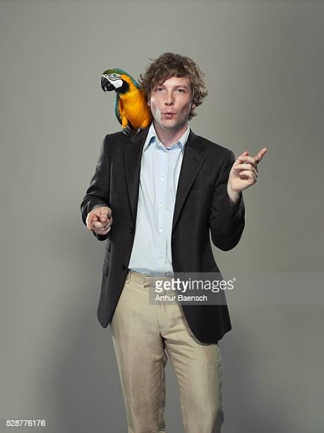 Parrot sitting on man's shoulder