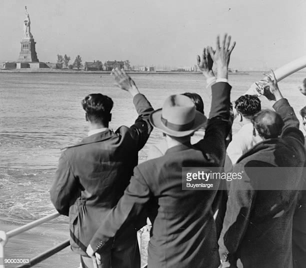 Part of a group of 171 aliens illegally in the country wave goodbye to the Statue of Liberty from the Coast Guard cutter that took them from Ellis...