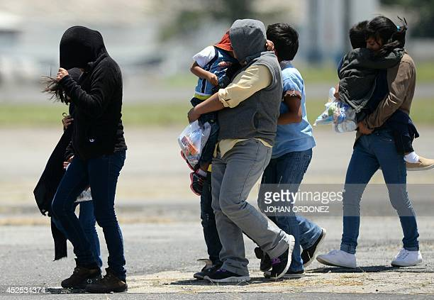 Part of a group of thirteen children aged between one and 13 and seven mothers walk upon arrival in Guatemala deported from the United States amidst...