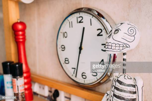 Part of a kitchen with clock, pepper pot and a mexican skeleton