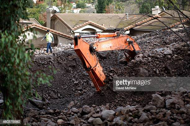 Part of a large backhoe is exposed as workers retrieve the machine that was buried under rocks and mud during a attempt to save homes from debris...
