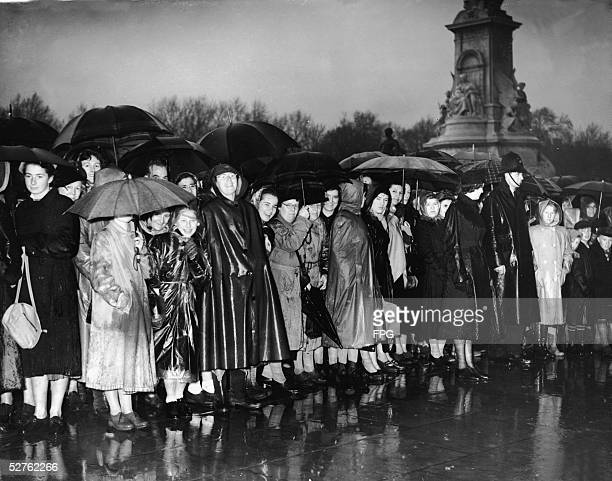 Part of a large crowd waits in the rain outside Buckingham Palace for the arrival of Princess Elizabeth and her husband the Duke of Edinburgh as they...