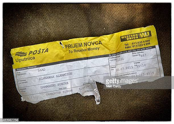 Part of a ripped up Western Union money transfer receipt from Damascus in Syria is seen after it was discarded beside railway tracks that run from...
