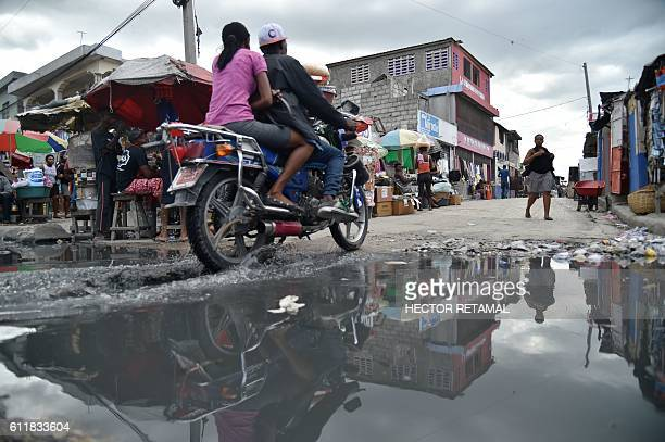 Part of a street is reflected in a puddle near the canal of Portail Leogane in the Haitian capital PortauPrince on October 1 2016 As Hurricane...