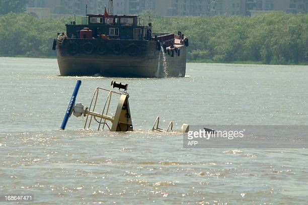 A part of a sunken vessel is seen on the water on May 13 2013 in Nanjing east China's Jiangsu province after it hit a bridge on the Yangtze River and...
