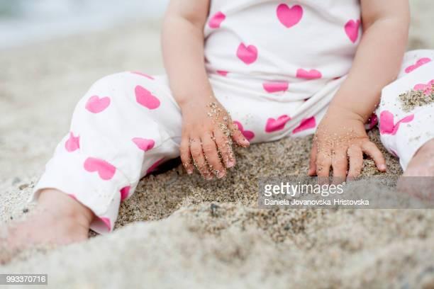 砂で遊ぶビーチで女の赤ちゃんの一部