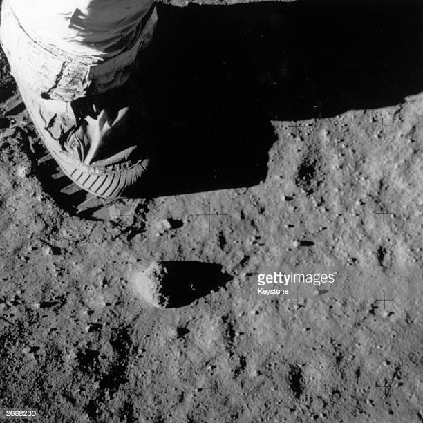 Part of Buzz Aldrin's leg foot and footprint on the surface of the moon during the Apollo 11 lunar mission