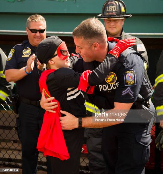 Part of his 'Make a Wish' wish Sawyer Fish 10 of Falmouth in action as Sonic Spider Boy hugs his partner Portland Police officer Rob Miller after...