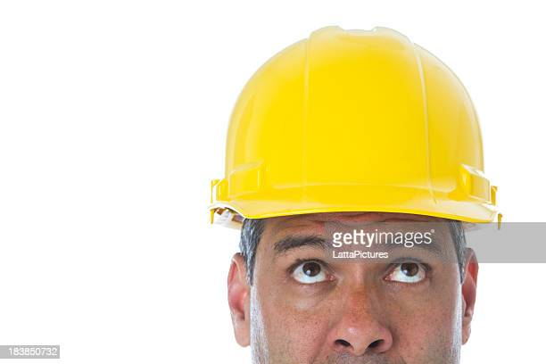 Part of man wearing hard hat looking up construction worker