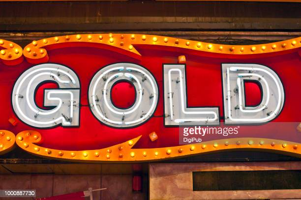 "Part of neon sign with a single word ""GOLD"""
