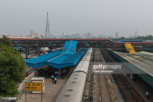 A part of New Delhi Railway Station with tracks and trains the skyline of Connaught Place in the hazy background