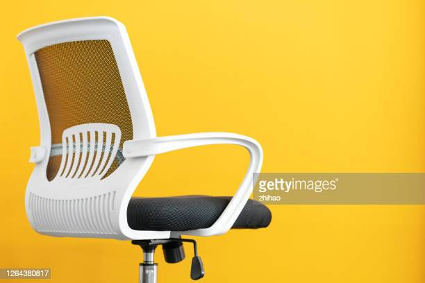 part of office chair in front of yellow background - 人間工学 ストックフォトと画像