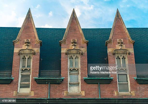 Part of the beautiful facade of the old building part of Toronto heritage with a roof over blue sky with white clouds