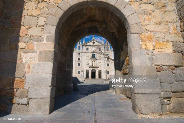 part of the city walls, saint's gate (puerta de la santa) and saint teresa church - avila stock photos and pictures