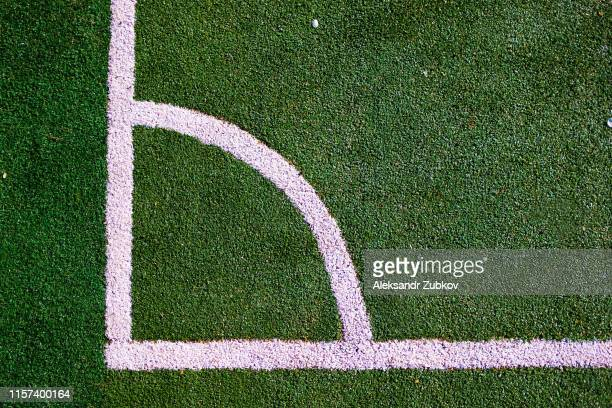 part of the layout of the football field, the position of the corner kick. white marking lines on the green grass of the sports stadium. - center athlete stock pictures, royalty-free photos & images