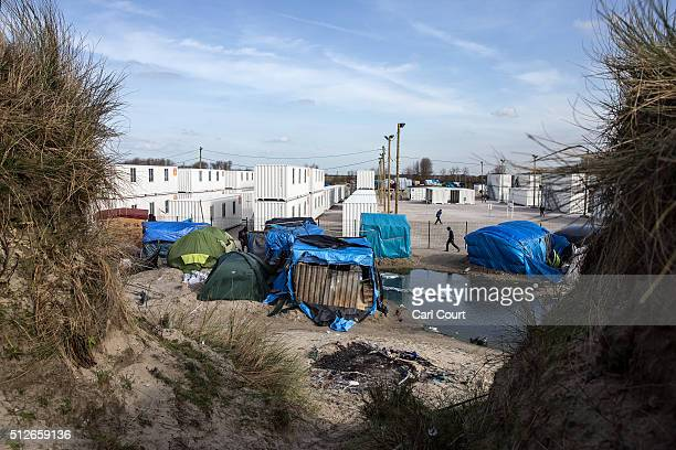 Part of the old 'jungle' camp is pictured next to new migrant accommodation on February 27 2016 in Calais France The French authorities have begun...