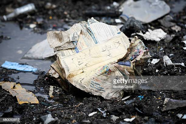Part of the yellow pages sits in the garbage that rests on top of the melting ice pile that remains of snow that was piled up from the city's winter...