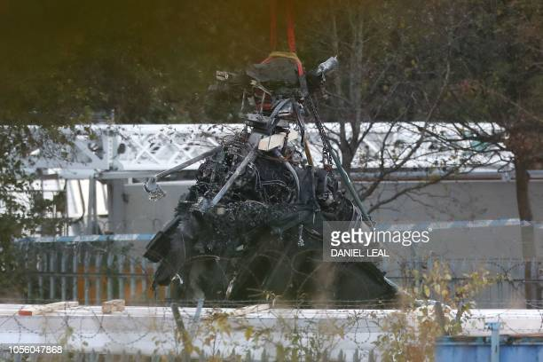 Part of what remains of the helicopter that crashed outside Leicester City Football Club's King Power Stadium is lifted with a crane at the crash...