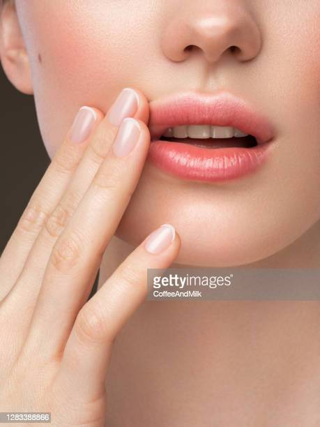 part of woman's face. woman's lips, nose and hand. soft skin. - lips stock pictures, royalty-free photos & images