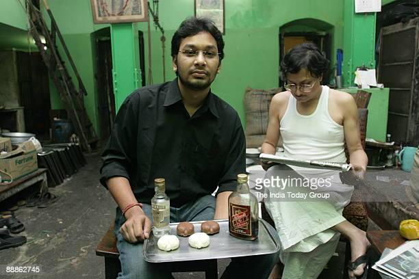 Partha Nandy holding the Alcoholic Sandesh on a trey while his uncle Prashanta Nandy watching it in Kolkata West Bengal India