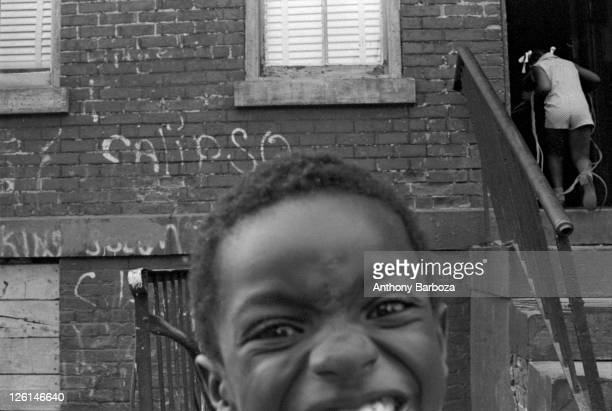 Partial closeup portrait of a young boy making a face towards the camera on an unidentifed Harlem street New York 1972 Behind him a young girl walks...