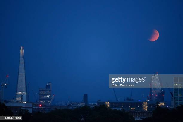 A partial lunar eclipse appears over the London skyline on July 16 2019 in London England Today marked the 50th anniversary of the launch of Apollo...